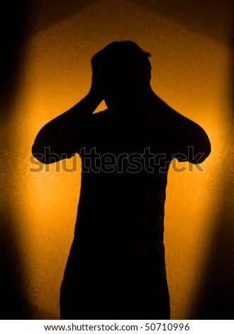 Depression and pain - silhouette of man in the darkness - stock photo