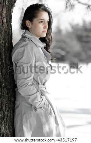 Depression series - desaturated image of young woman alone in winter scene - stock photo