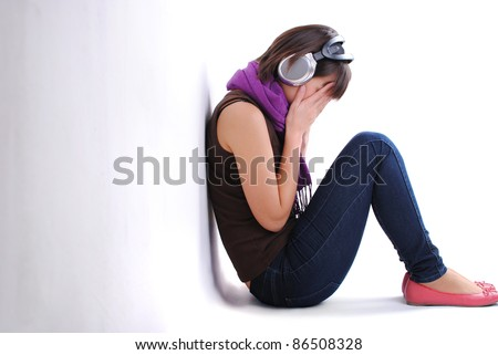 depression teen girl listening to music and cried lonely in room - stock photo