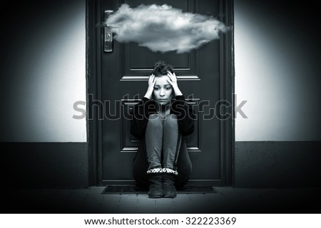 Depressive woman at the doorstep with cloud above her head. - stock photo