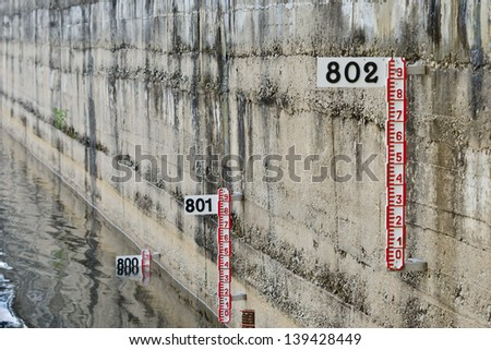 depth marker on the wall of a swamp - stock photo