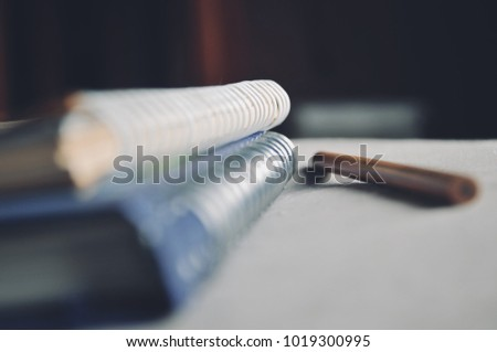 Depth of field of Loop binding book and pencil on the bed with light from the window on the morning concept of education and business