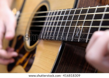 Depth of field of man play acoustic guitar close up with selective focus