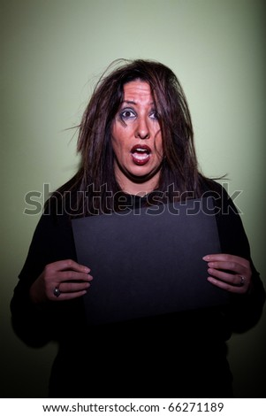 Deranged looking woman in mugshot with blank board - stock photo