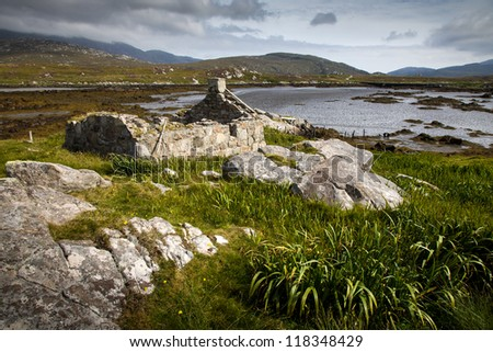 Derelict crofters cottage by a loch - stock photo