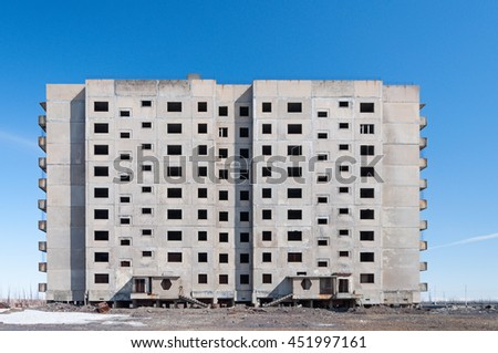 Derelict high-rise building in Norilsk. House on pile foundation, built on permafrost. - stock photo