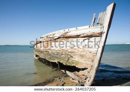 Derelict wooden oyster boat left rot away on beach at Ocean Beach Road, Bluff, Invercargill, New zealand. - stock photo