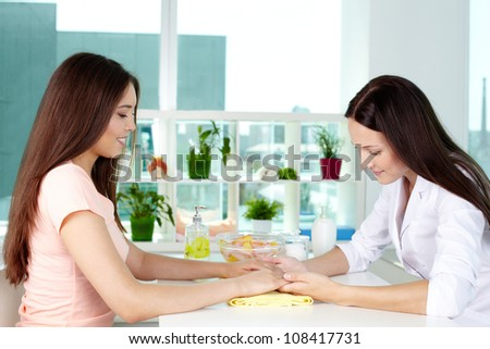 Dermatologist consulting her client on hand care - stock photo