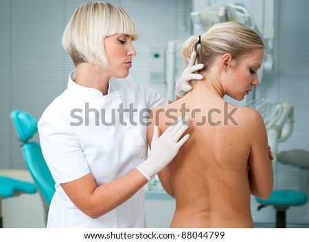 dermatologist doctor inspecting woman patients skin on her back - stock photo