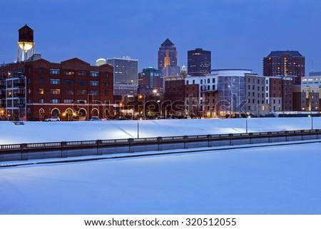 Des Moines skyline across frozen river. Des Moines, Iowa, USA. - stock photo