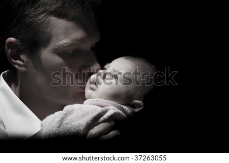 Desaturated capture of a father holding his newborn baby, with light focused on the baby - stock photo