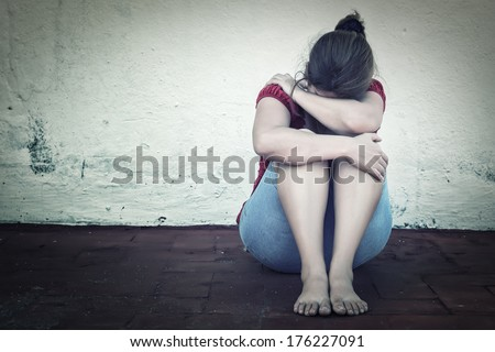 Desaturated grunge image of a very sad adult woman crying - stock photo