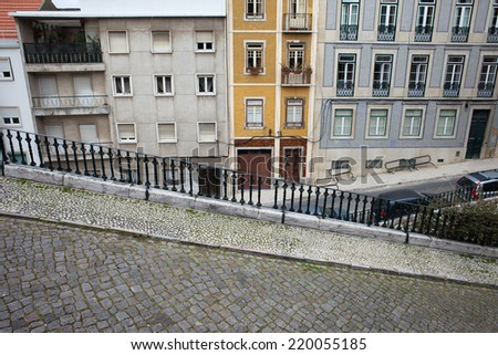 Descending, steep, cobbled street with sidewalk and houses in the background in Lisbon, Portugal.