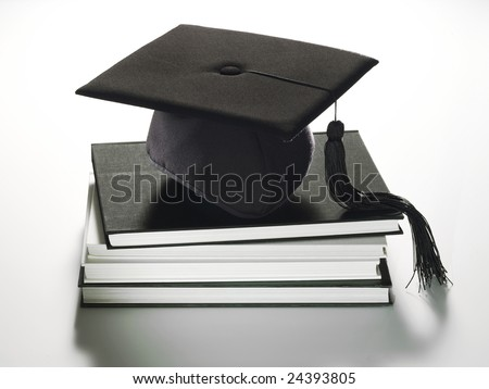 Description: A graduation hat sitting on a stack of books. - stock photo