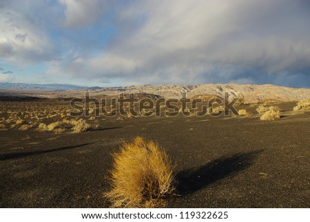 Desert and mountains under threatening skies near Ubehebe Crater, Death Valley, California - stock photo