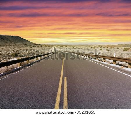 Desert highway at sunset - stock photo