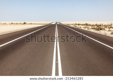 Desert highway in Abu Dhabi, United Arab Emirates - stock photo