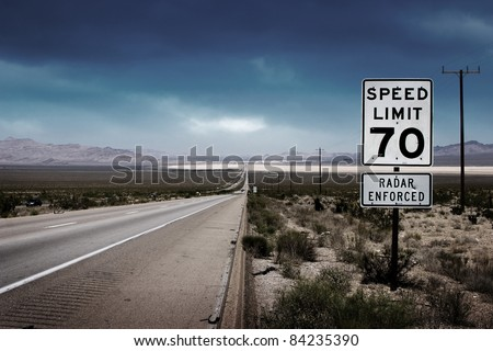 Desert highway road to horizon with a speed limit sign on a side. - stock photo