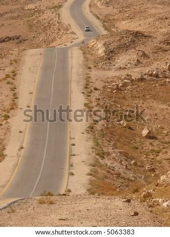 Desert highway with a car approaching, arid soil, stone desert, King's Highway, Jordan, Middle East - stock photo