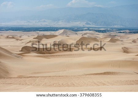 Desert in Huacachina, Peru. Buggy road and dunes in background - stock photo