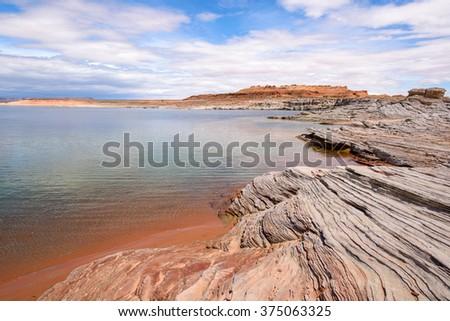 Desert Lake - Dramatic and colorful sandstone rocks at the shore of Lake Powell. Glen Canyon National Recreation Area, Page, Arizona, USA. - stock photo