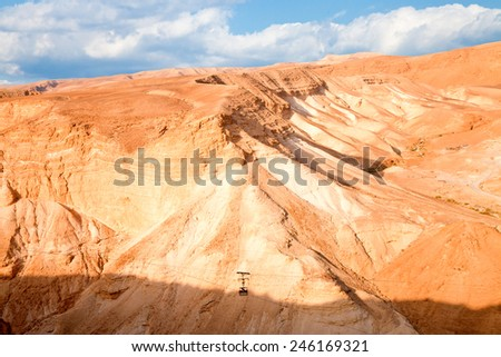 Desert mountain scenic with soft cloudscape and forgotten cable trolley - stock photo