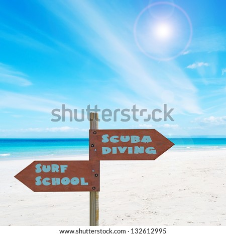 desert paradise beach on a clear day with a wooden sign - stock photo