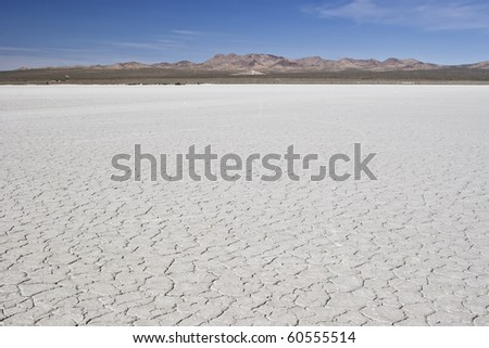 Desert revealing cracked earth, mountains and blue sky