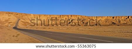desert road and traffic signs in arabic in the Arabian Desert in Saudi Arabia, slope in the background - stock photo