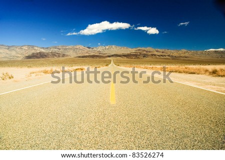 desert road in Death Valley, CA with unique cloud formation