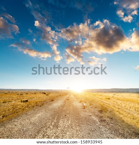 desert road, white clouds and deep blue sky - stock photo