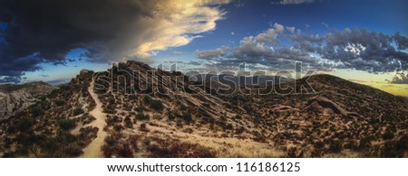 Desert road with clouds - stock photo