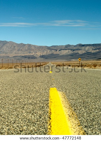Desert road with mountains and power lines through Death Valley National Park, California - stock photo