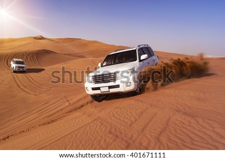 Desert Safari SUVs bashing through the arabian sand dunes - stock photo