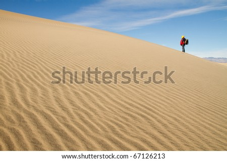 Desert Sand Dune with a Lone Hiker in the Distance. - stock photo