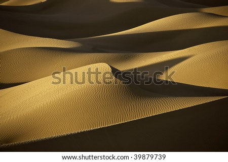 desert sand dunes in evening light with shadows in the Sahara - stock photo