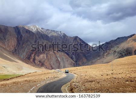 Desert scenic view of high mountain winding road and a car against the background of rugged mountain wall and dramatic cloudy sky in Pangong range, Ladakh, Himalaya, Jammu & Kashmir, Northern India  - stock photo