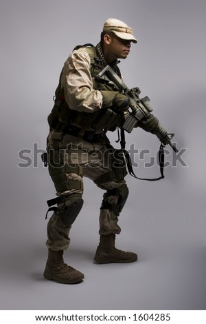 desert storm soldier in the army dressed in camo in stalker position - stock photo