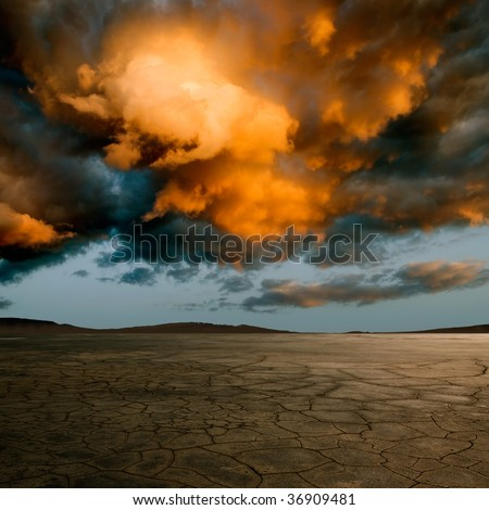 Desert with cracked ground and dramatic clouds. - stock photo