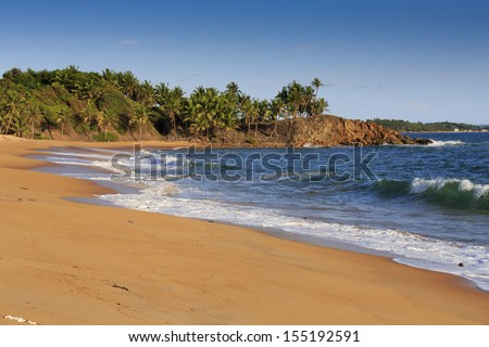 Deserted African beach with sand and rocky coastline at sunset in Axim, Ghana - stock photo