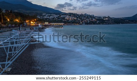 Deserted beach and city lights at night - stock photo