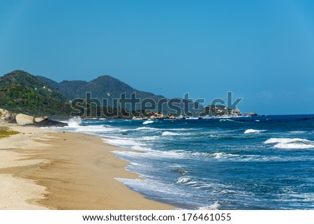 Deserted beach and deep blue Caribbean water in Tayrona National Park in Colombia