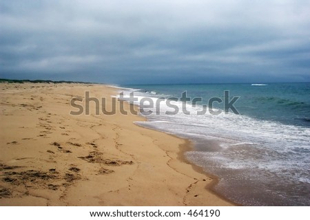 deserted beach on cloudy day - stock photo