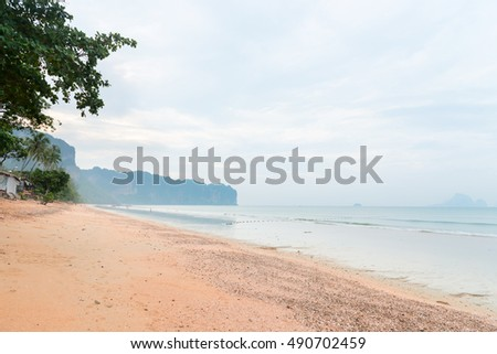 Deserted beach with trees and a head land in the distance, clean sand outdoors with a hazy sky.