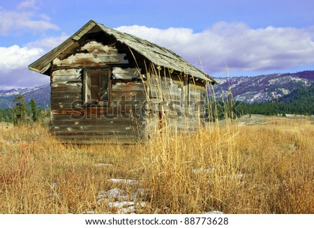 Deserted Cabin:  An old wooden cabin, falling to ruin, stands on a grassy hillside. - stock photo