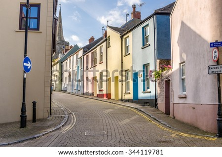 Deserted Cobbled Street Lined with Pastel Terraced Houses in Wales - stock photo