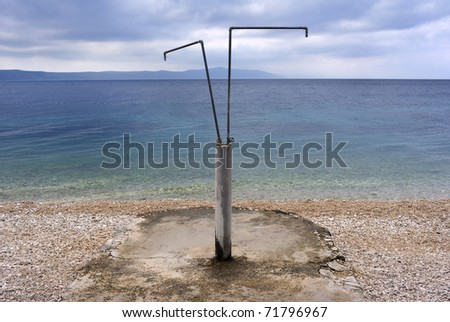 Deserted Croatian beach with shower in the summer. - stock photo