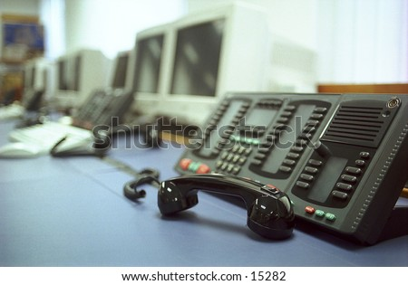 Deserted desk in an office environment with phones off the hook and computers switched off - stock photo