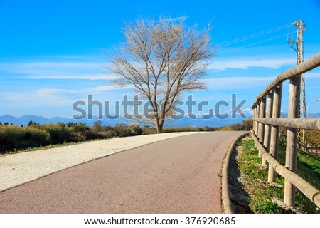 Deserted  hiking path  near river with snowy mountains peaks in background - stock photo