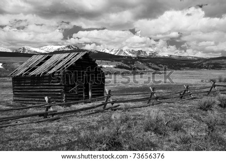 Deserted house on a empty field, Rocky Mountains in the beckground - stock photo